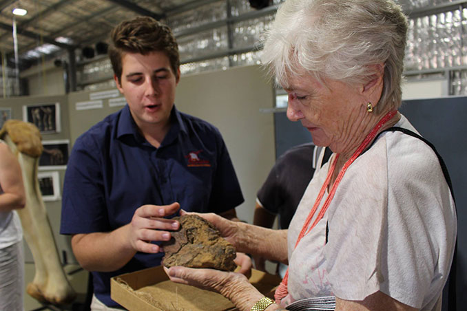 Staff member talking to visitor about fossils at Eromanga Natural History Museum